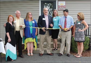image of President Jeff Thomas (center) cuts the ribbon with SHINE Systems's finance department employees.
